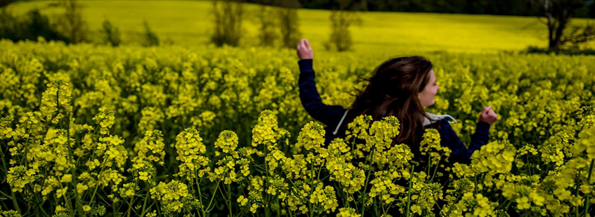 woman running through a field of flowers