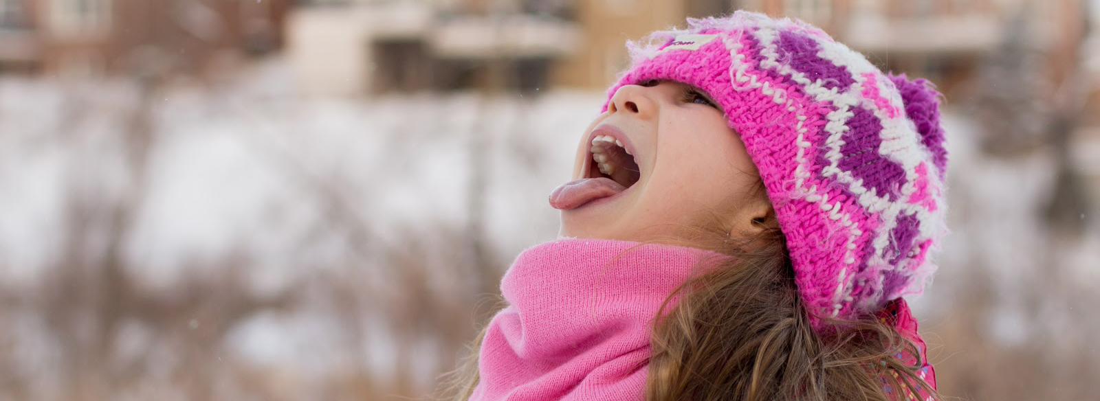a girl wearing a pink hat catching snowflakes