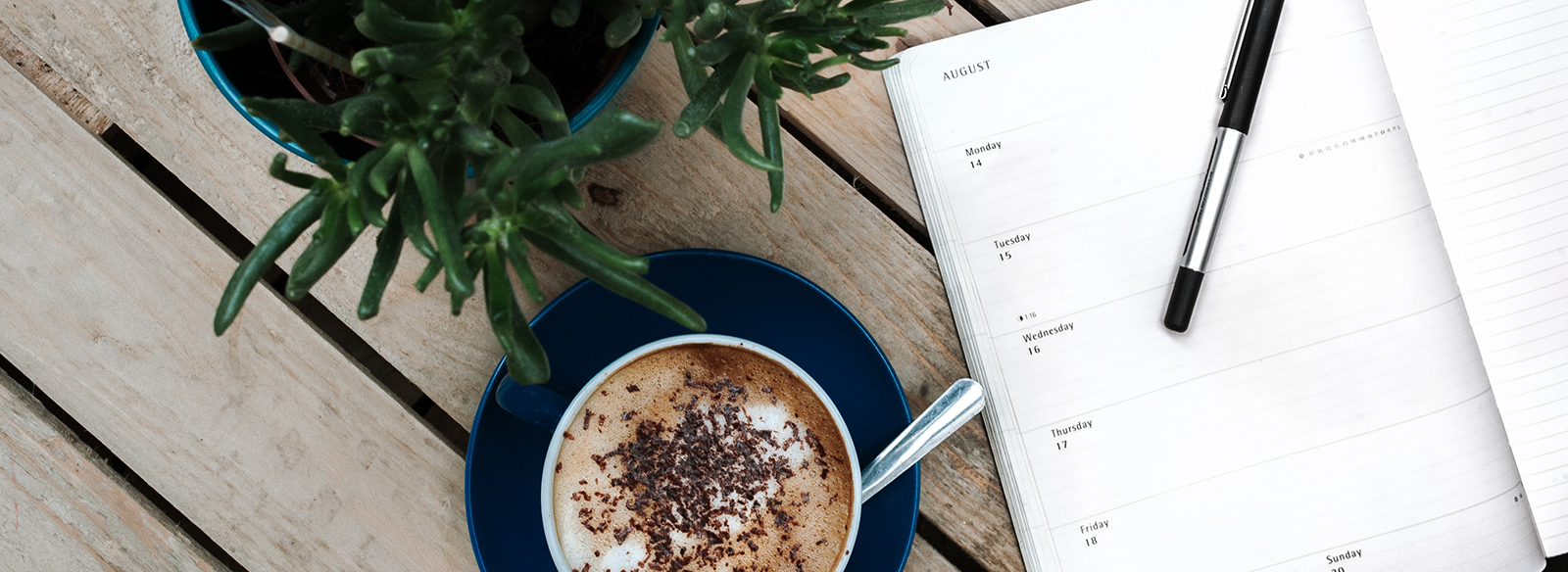 a planner, a pen, a coffee and a pant on top of a table