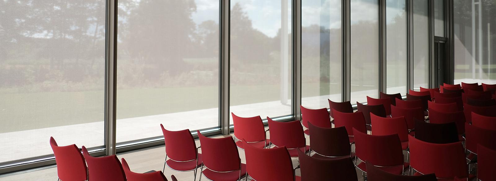 rangées de chaises rouges mises en place pour une conférence