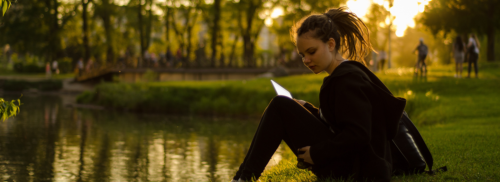 jeune femme lisant et assis sur une rive