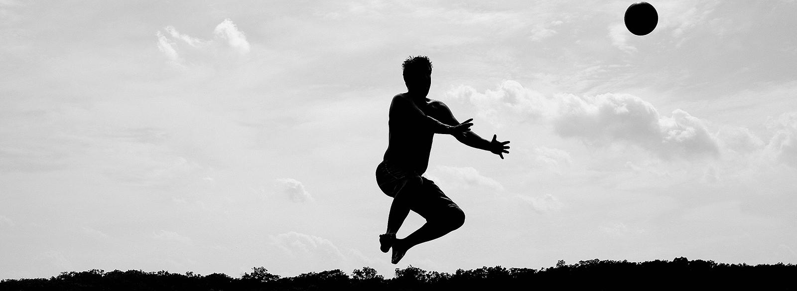 homme sautant en lançant une balle