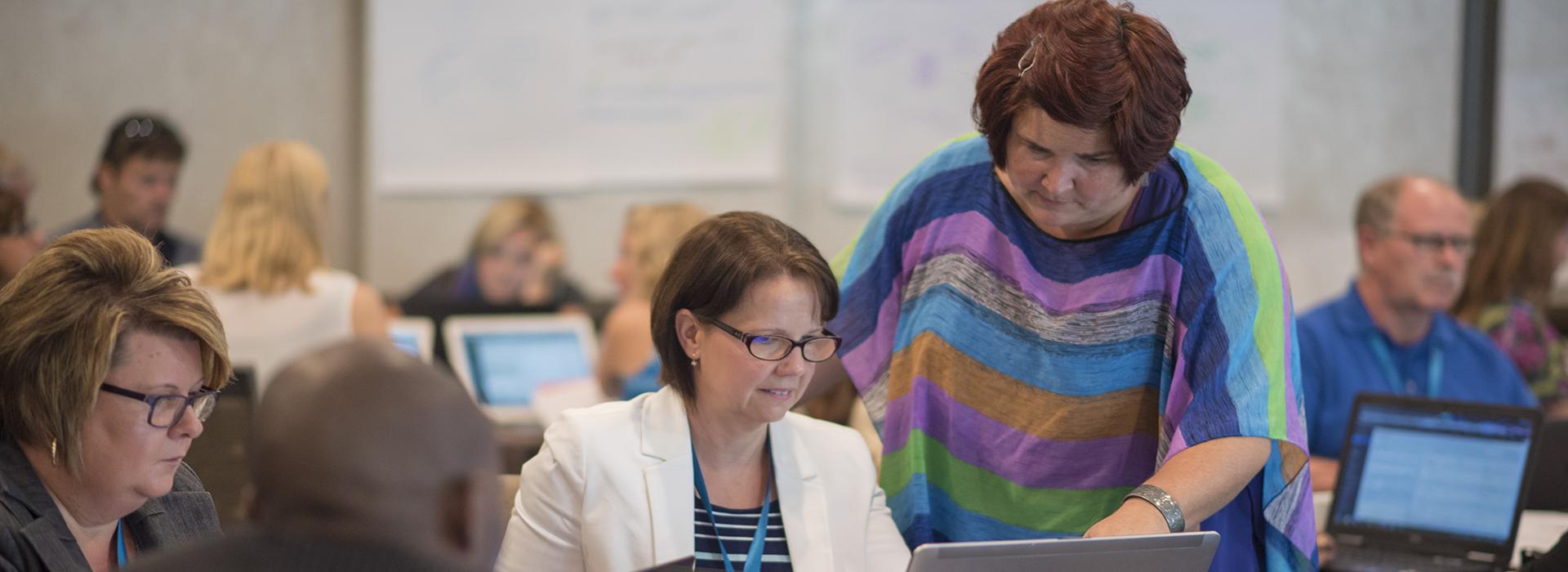 Une femme assite un autre femme sur le lab d'ordinateur