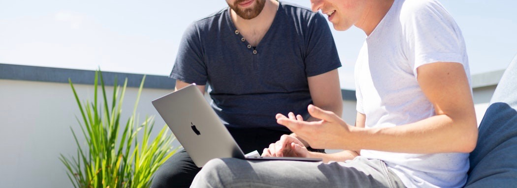 Deux jeunes hommes avec un ordinateur portable.