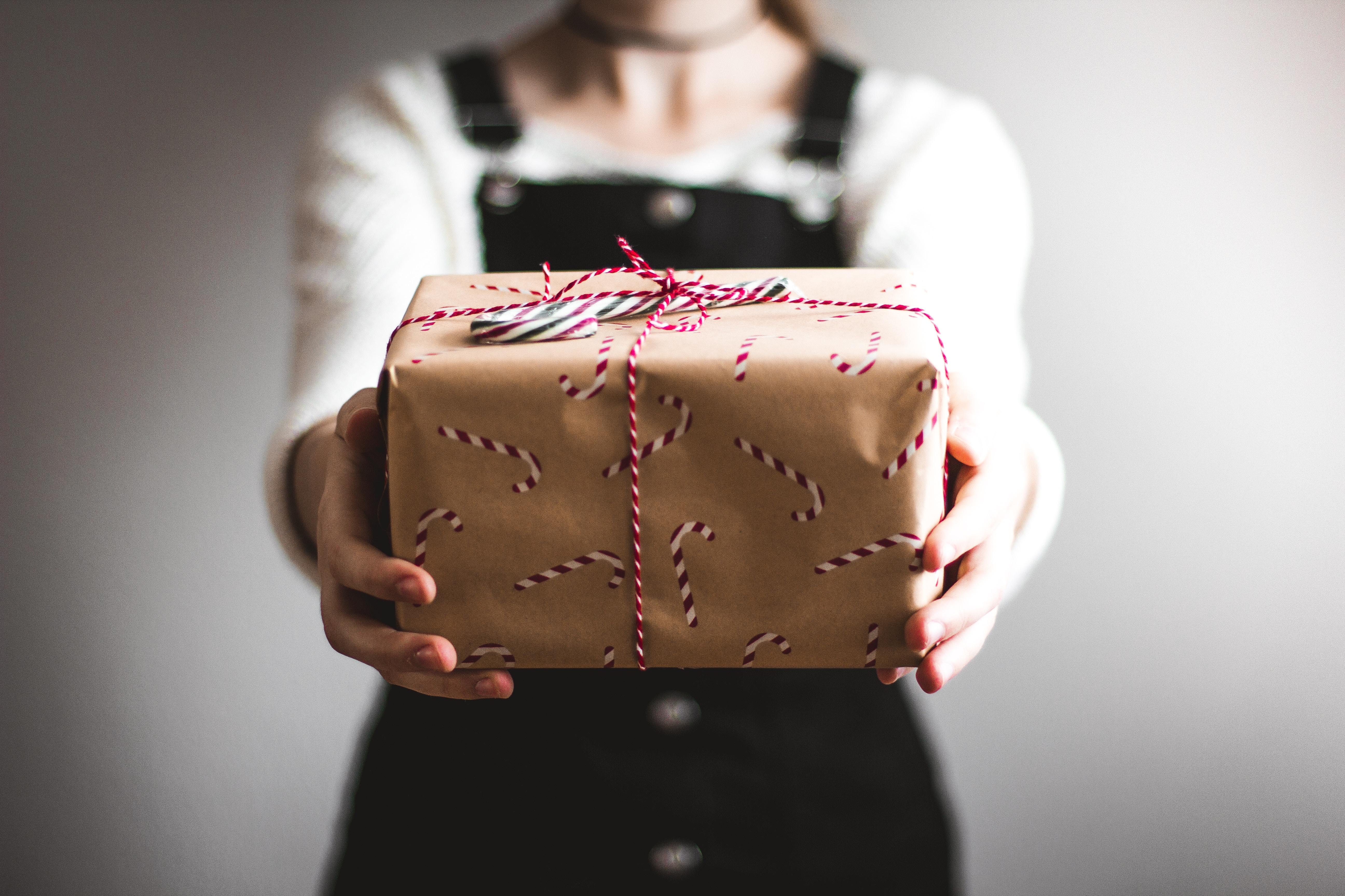 personne montrant une boîte cadeau brune