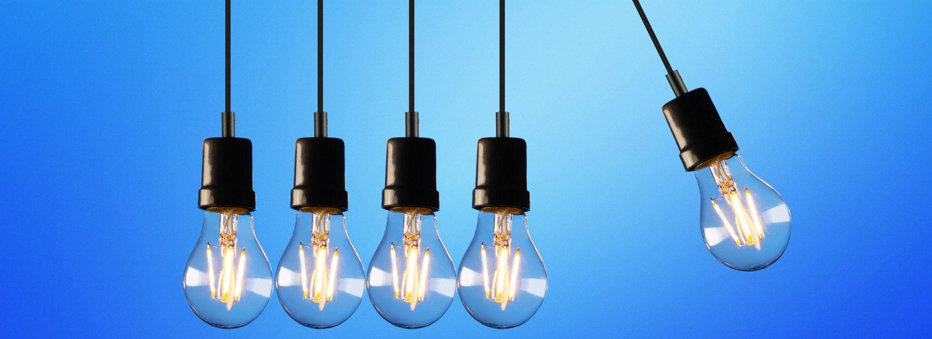 5 ampoules suspendues sur fond bleu vif