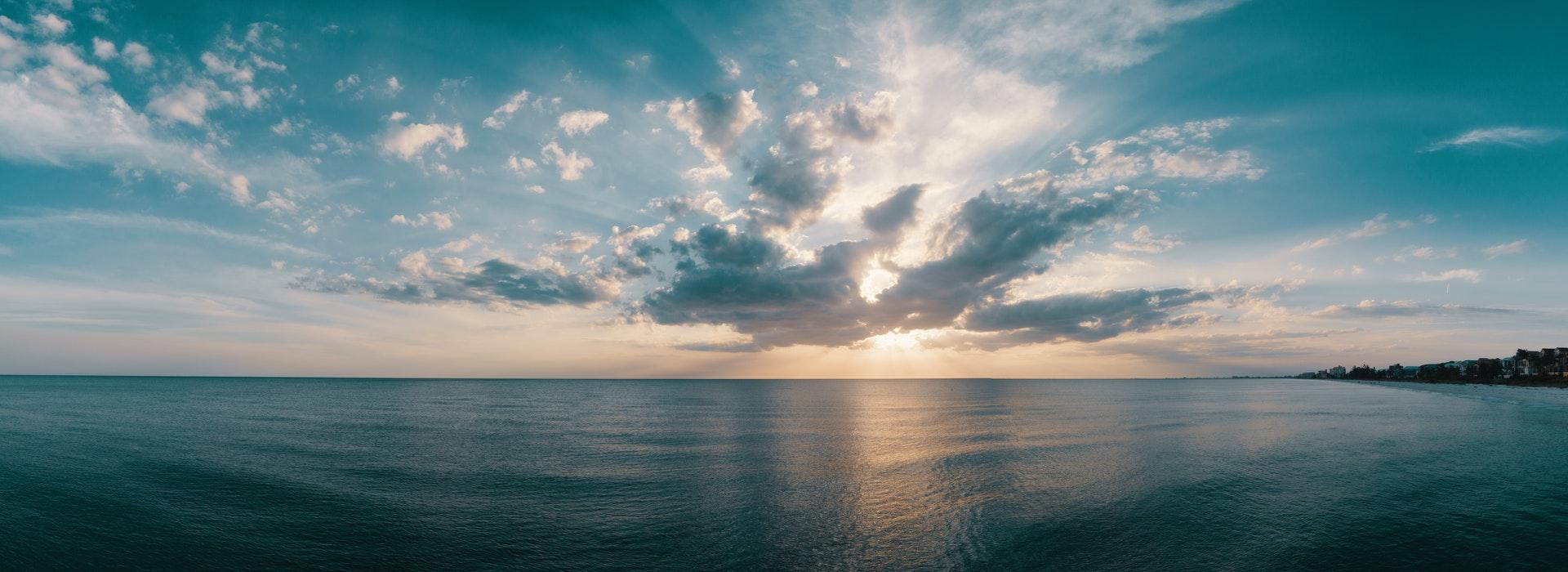 Nuages cotonneux au-dessus d'un océan bleu foncé au coucher du soleil.
