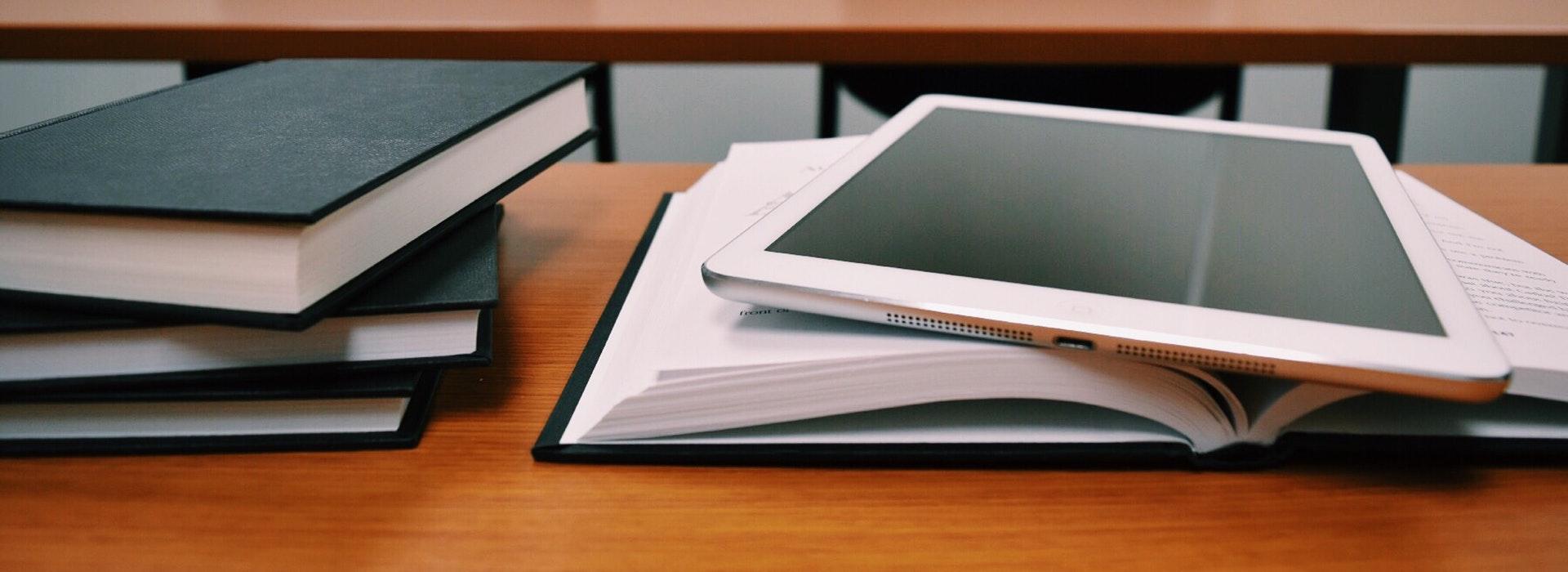 Livres noirs et un iPad blanc empilés sur un bureau en bois.