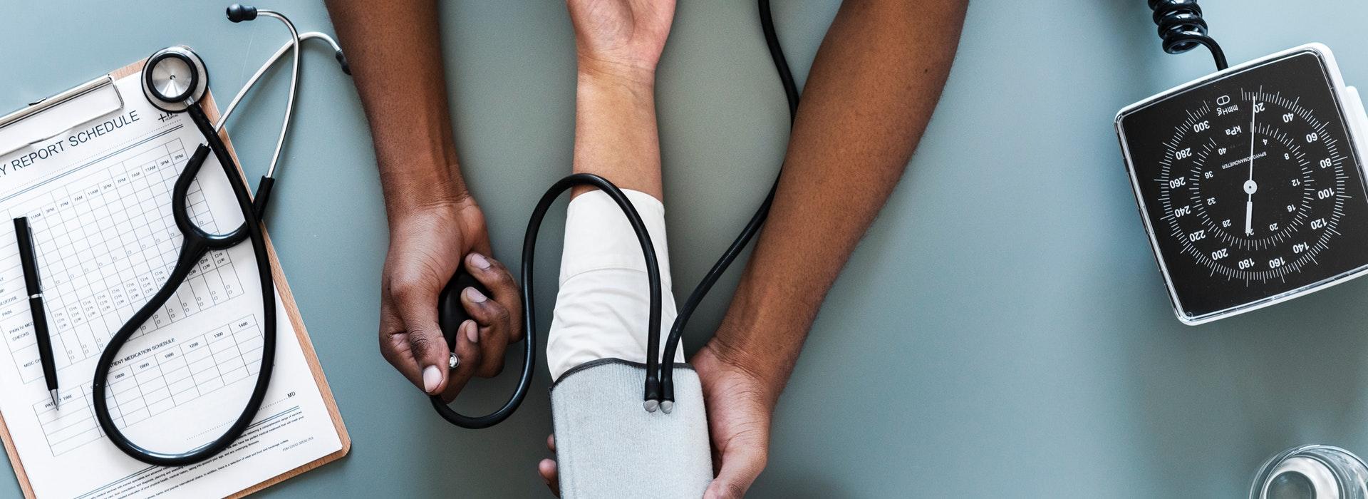 English description: Bird's eye view of a nurse's hands using a black blood pressure monitor on a patient's arm. description en français: vue des mains d'une infirmière qui utilise un tensiomètre noir sur le bras d'un patient.