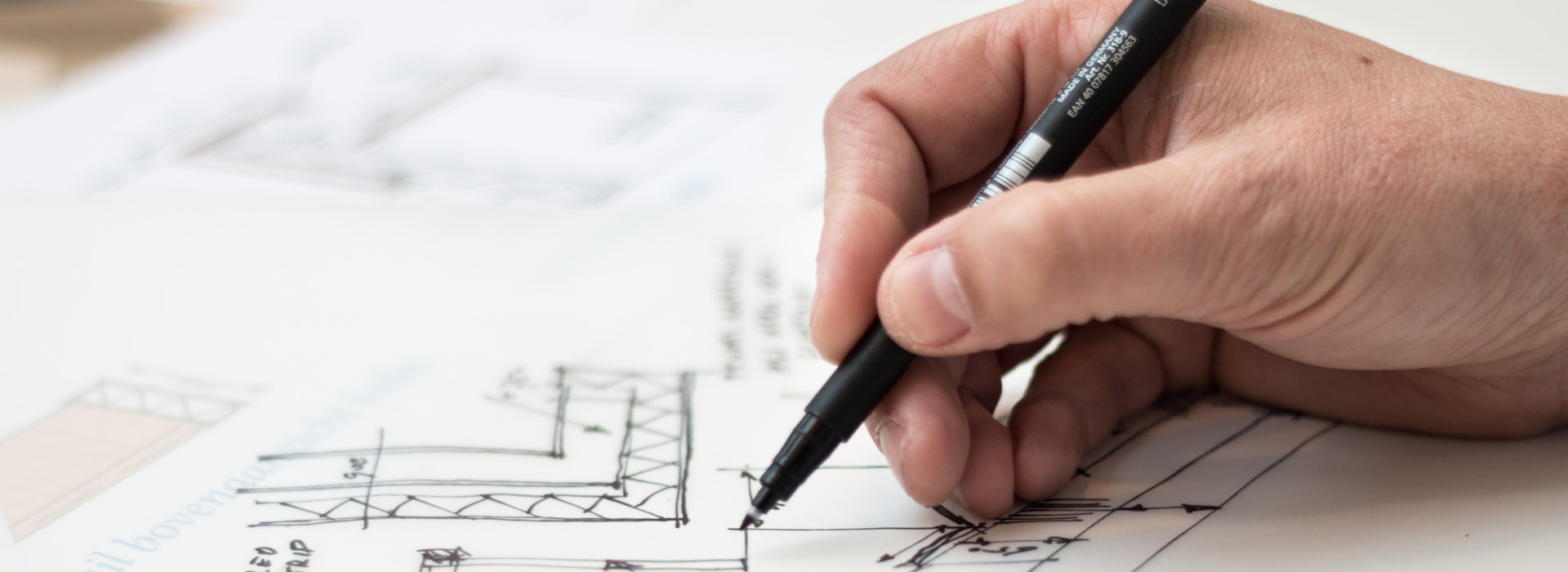 A man's hand holds a black pen over an architectural diagram