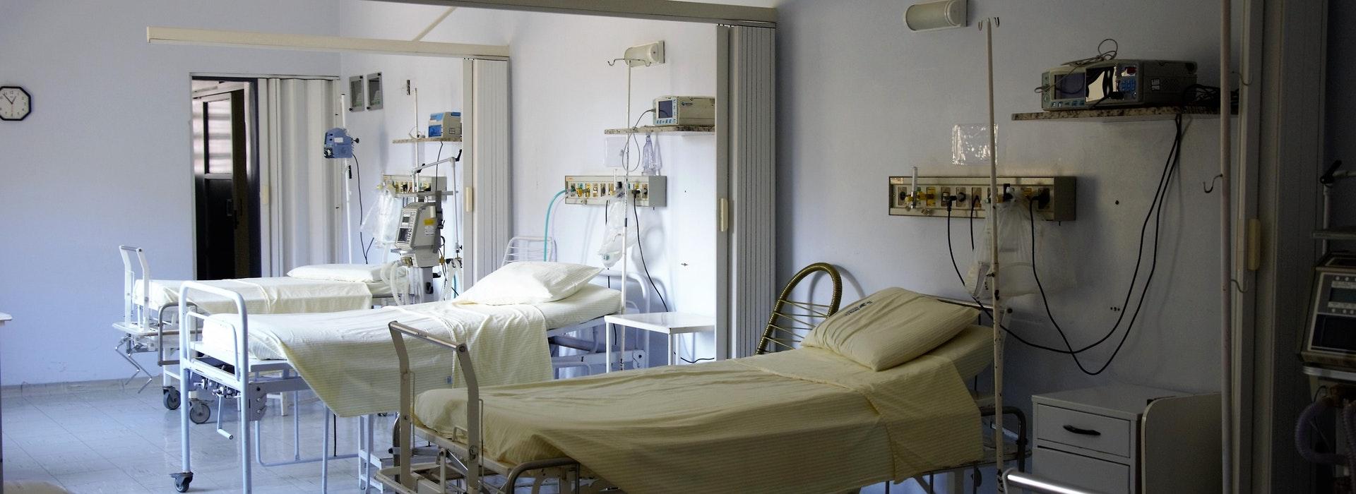 Trois lits vides, côte à côte, dans une chambre d'hôpital