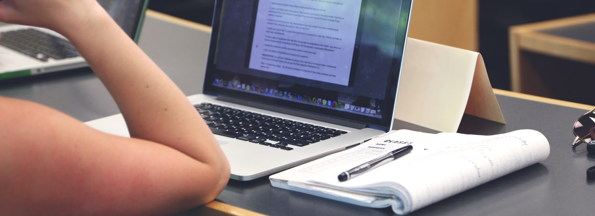 Close up of a person's arm resting on a desk with a laptop and notebook
