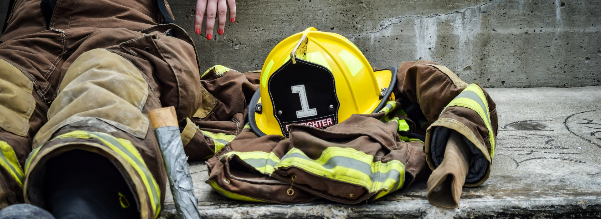 A yellow hardhat and firefighter's jacket sits next to a firefighter sitting on the ground