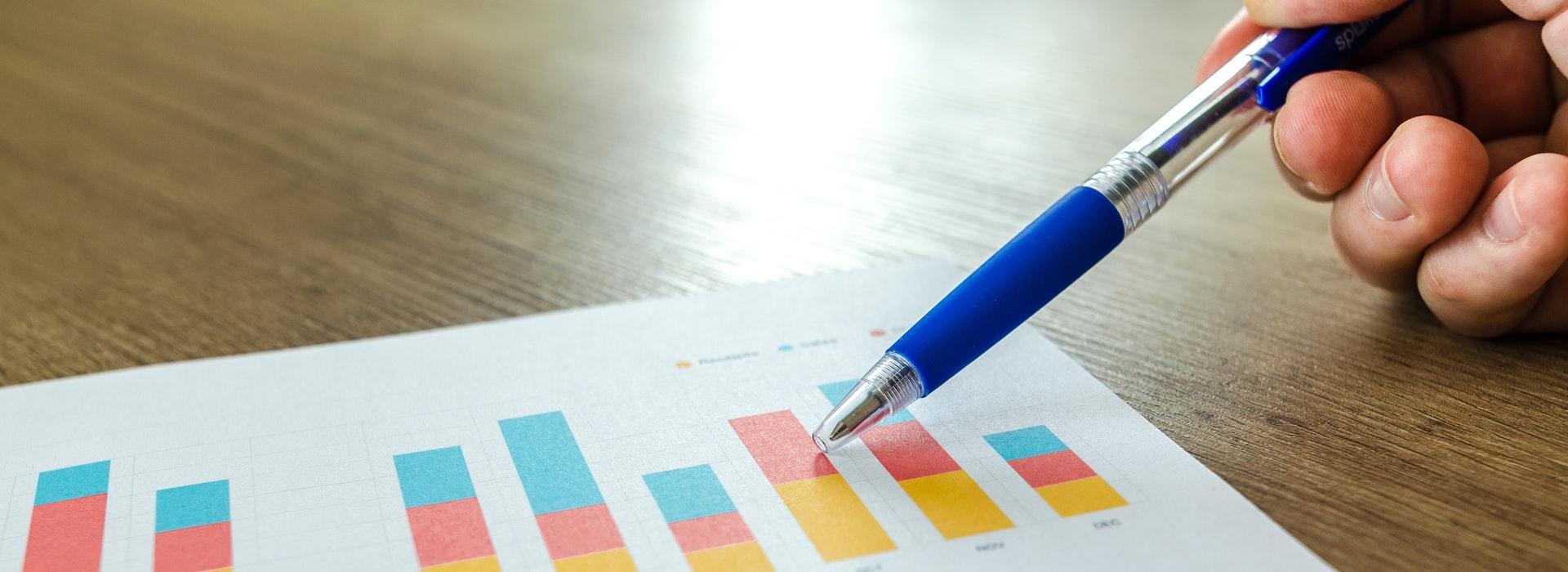 Main tenant un stylo au-dessus d'un graphique à barres bleu et orange