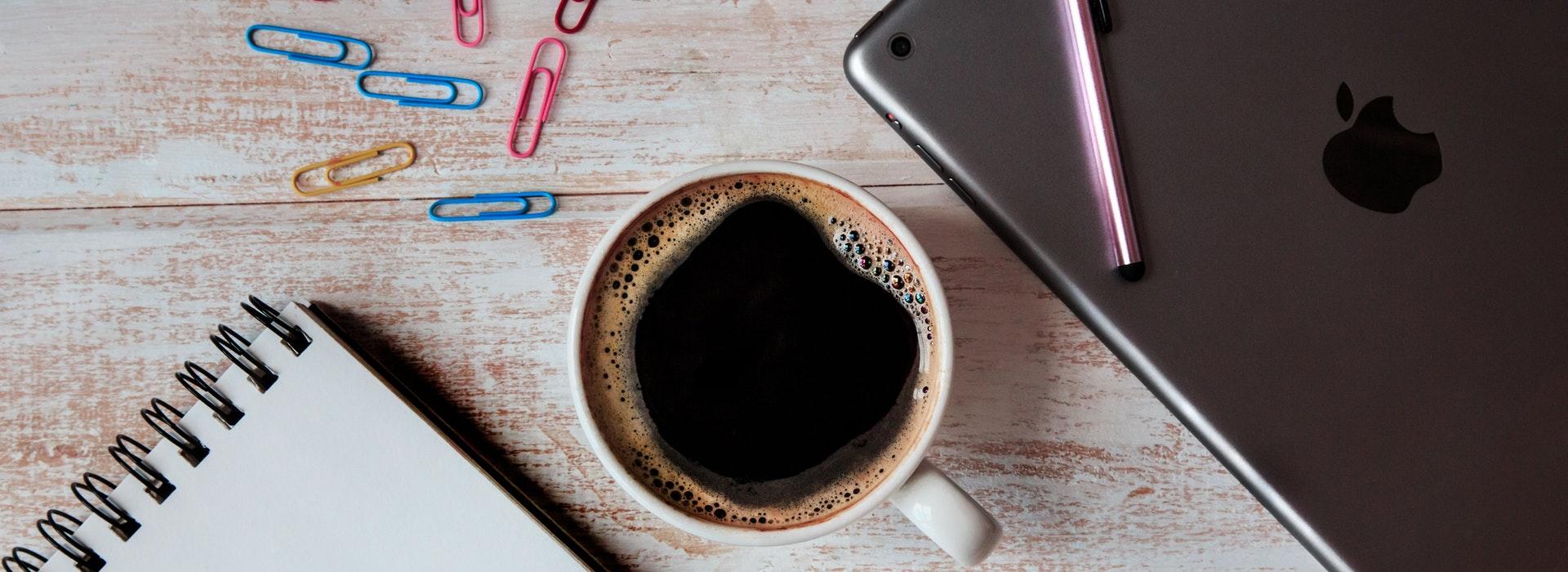 Un ordinateur portable argenté, des pinces à papier colorées et une tasse de café sont disposés sur un bureau blanc