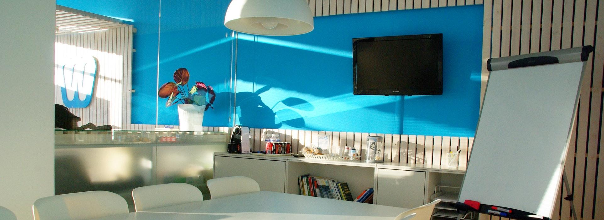 Photo de chaises blanches dans un bureau contre un mur bleu