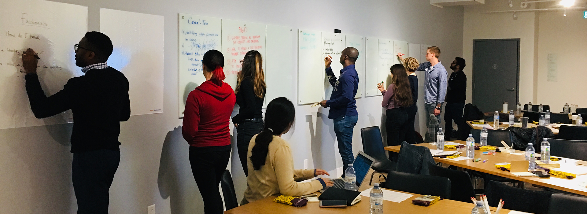 Students stand, writing on a whiteboard