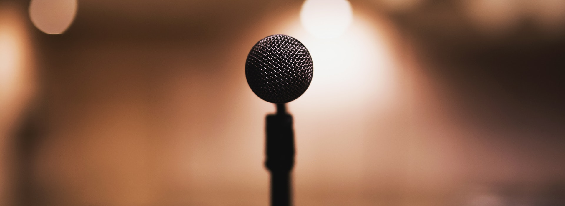 Closeup photo of a microphone against a blurry brown background