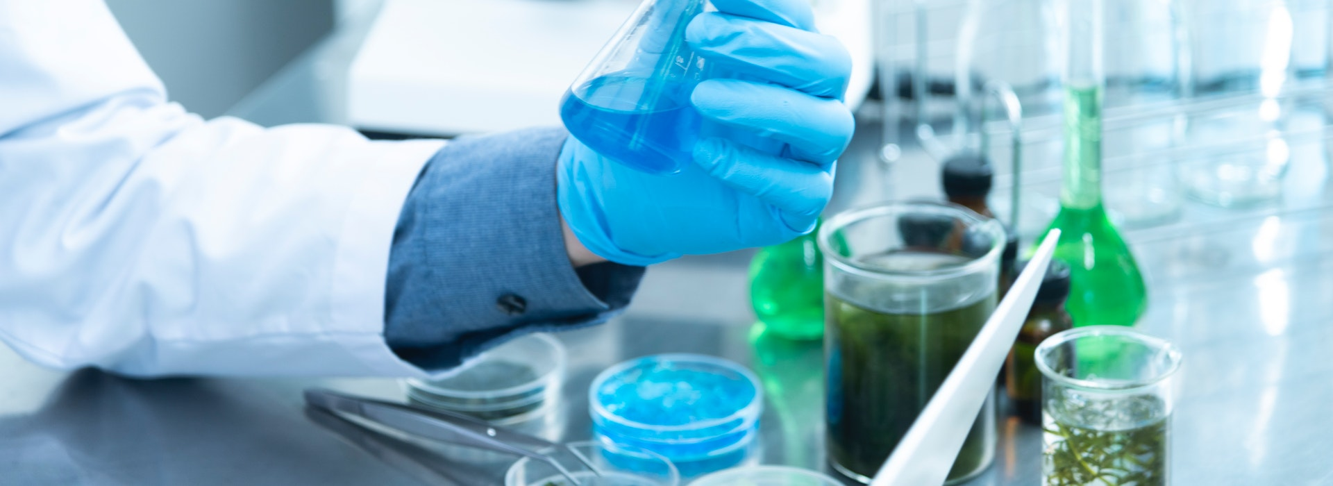 Photo of a blue gloved hand holding a chemical testube