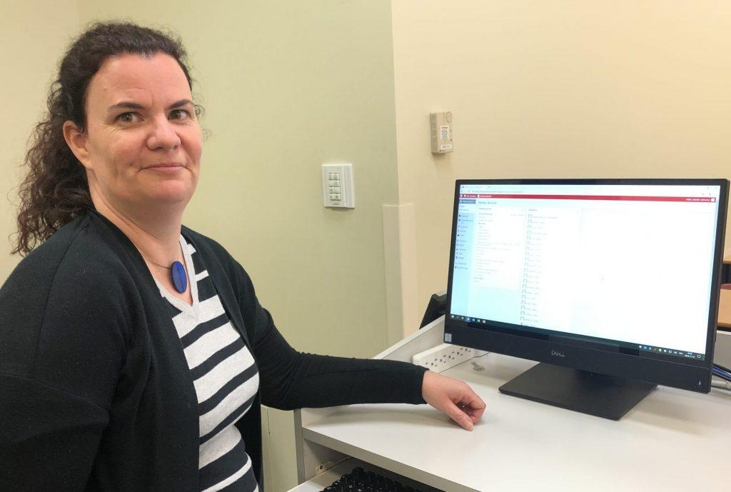 une femme aux cheveux noirs est assise devant un ordinateur, souriant