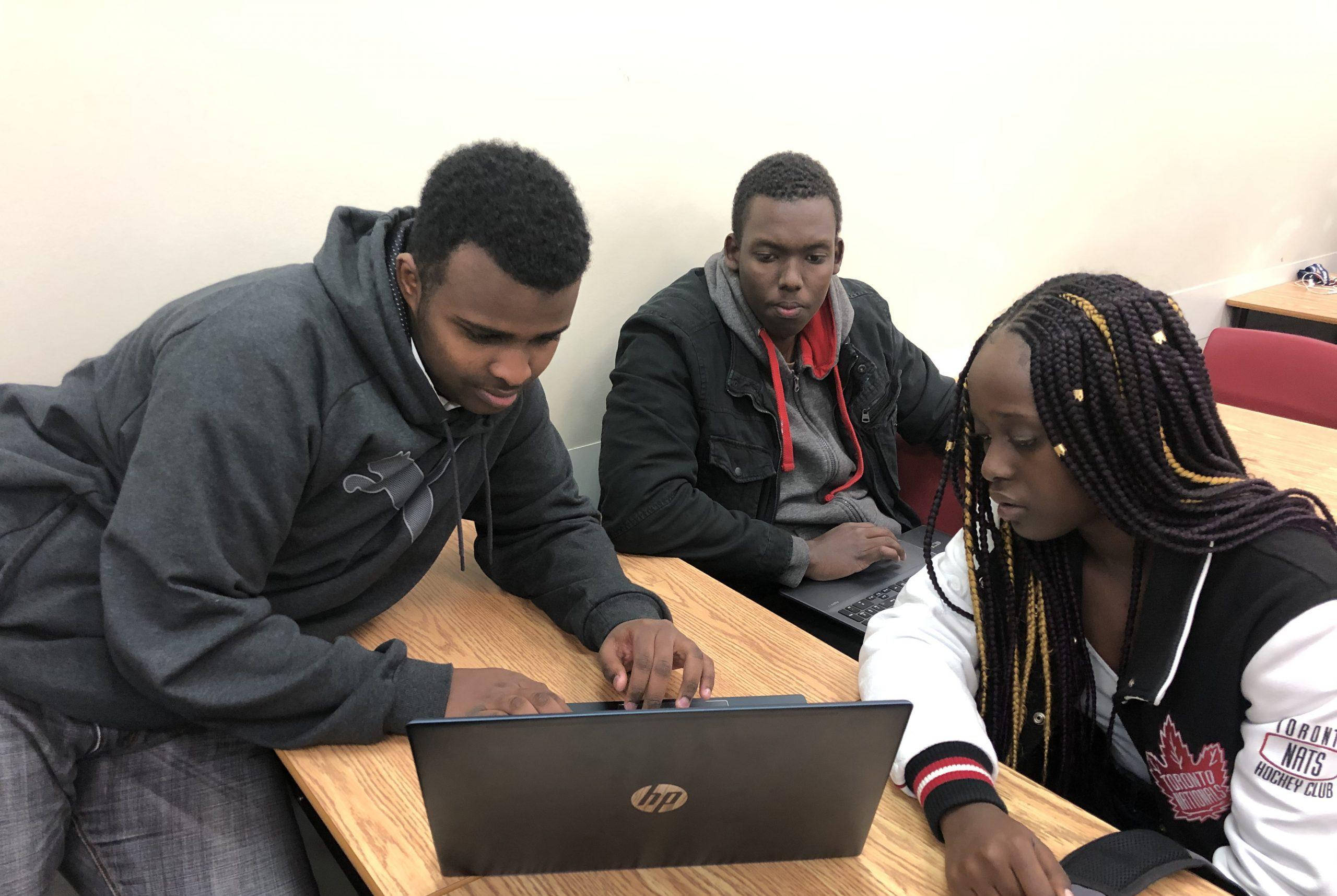 trois étudiants aux cheveux noirs regardent un ordinateur portable