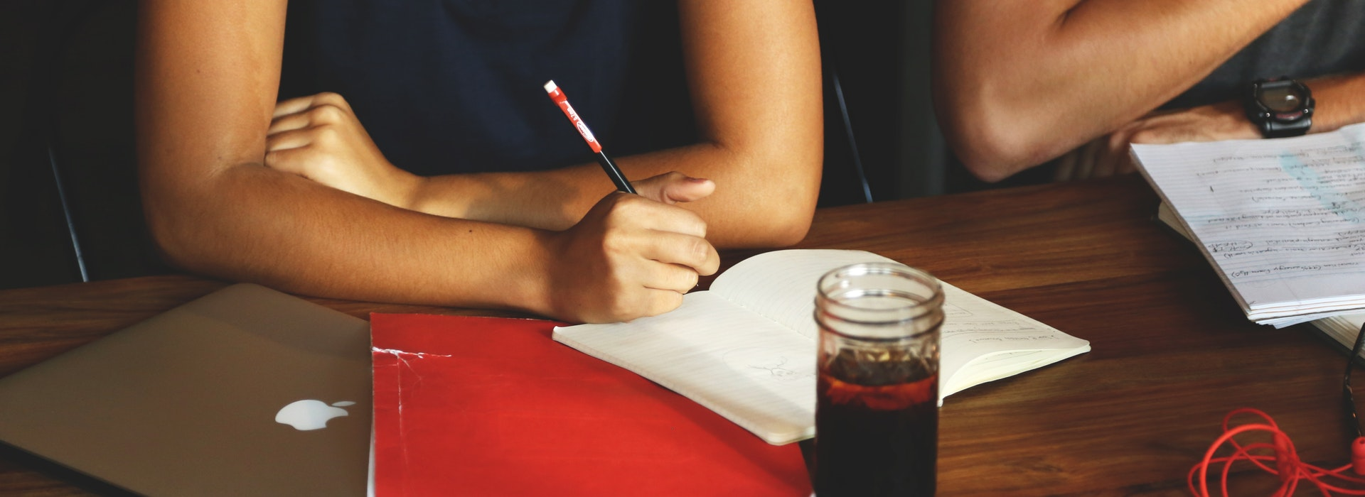 Closeup photo of a woman writing in a red notebook on a desk with a cup of coffee in front of her