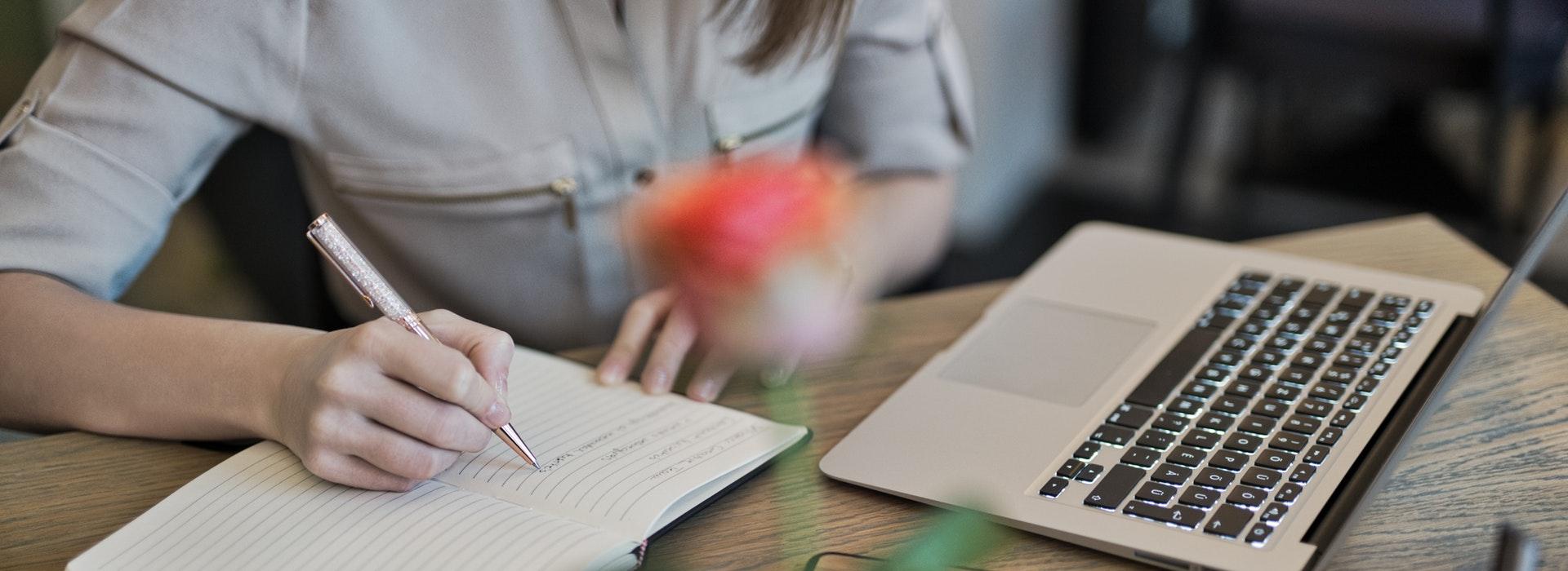 Photo en gros plan des mains d'une femme qui écrit dans un carnet à côté d'un ordinateur portable