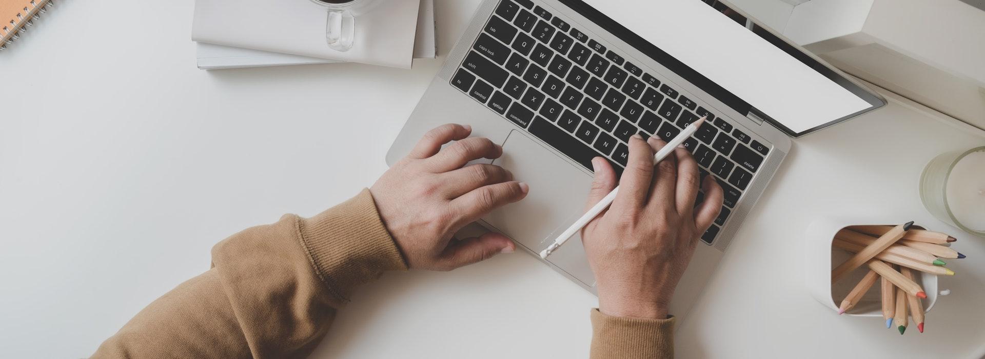 Deux mains sur un clavier à côté d'une tasse de café