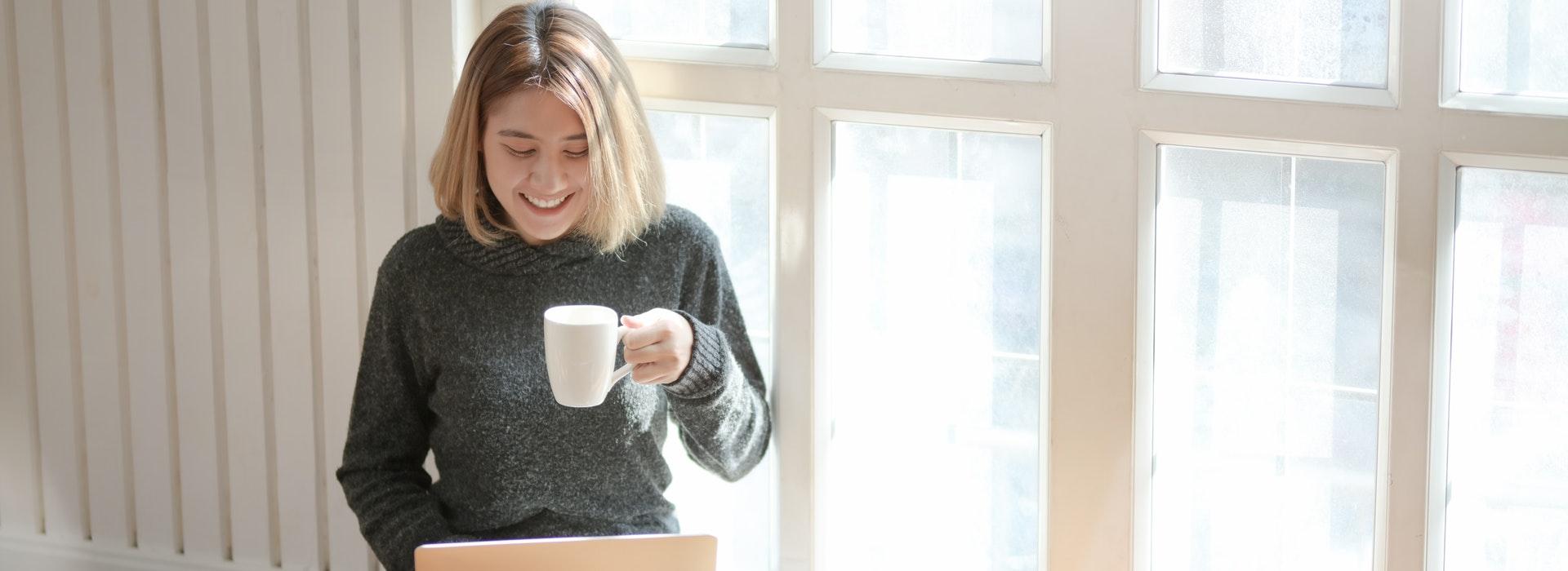 Une femme assise à une fenêtre boit du café et tape sur un ordinateur portable