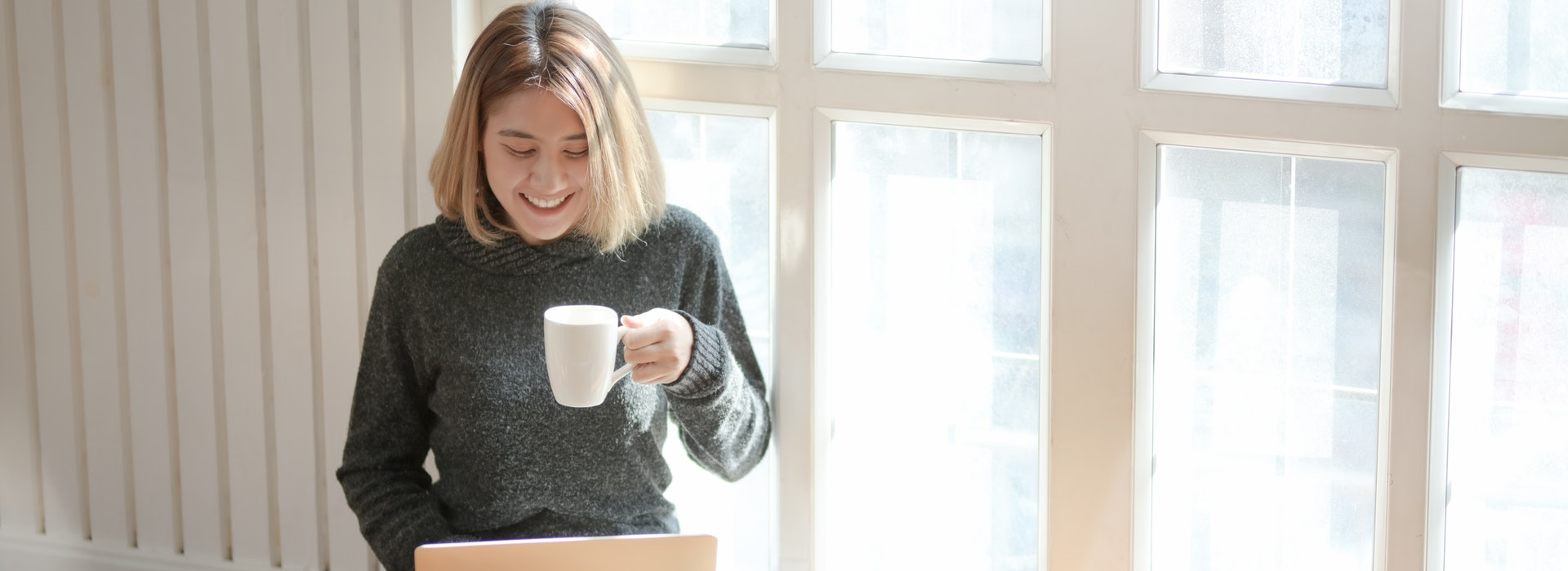 A woman sits in a window, drinking coffee and typing on a laptop