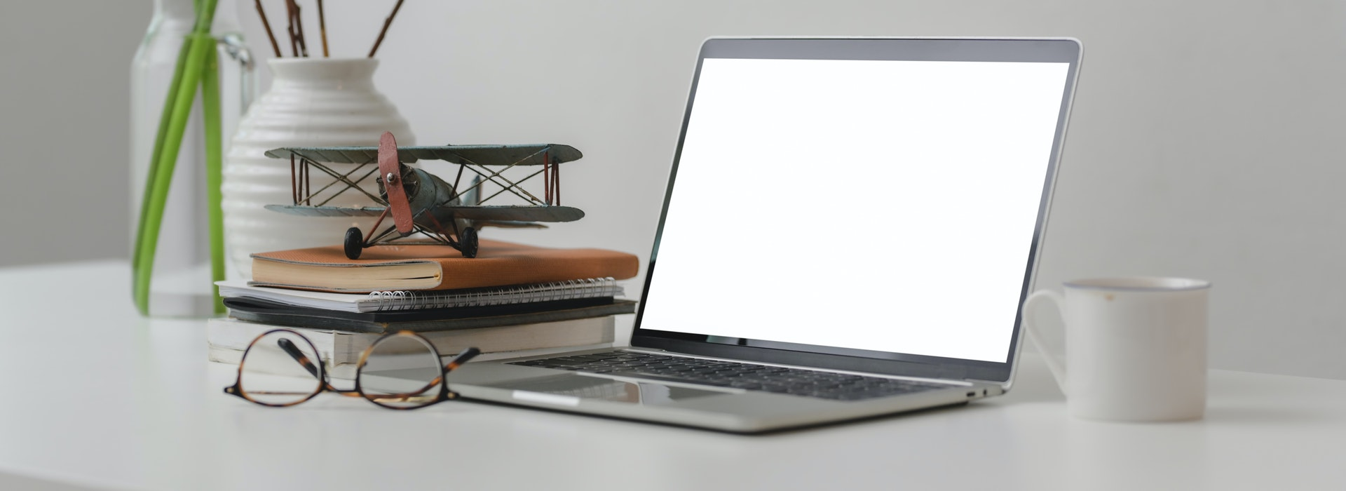 Photo of a latop and books on desk