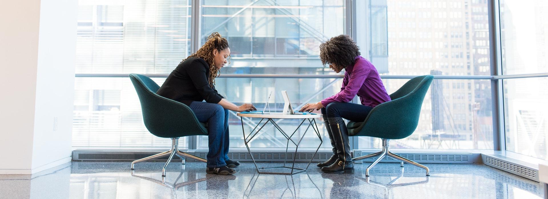 Deux femmes sont assises en face l'une de l'autre, travaillant sur des ordinateurs portables
