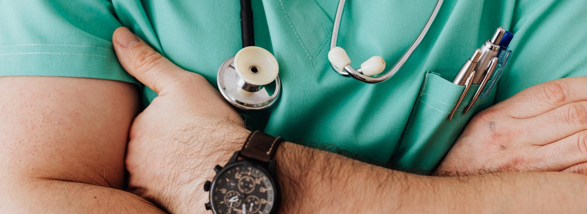 gros plan sur le torse d'un homme portant une blouse médicale verte